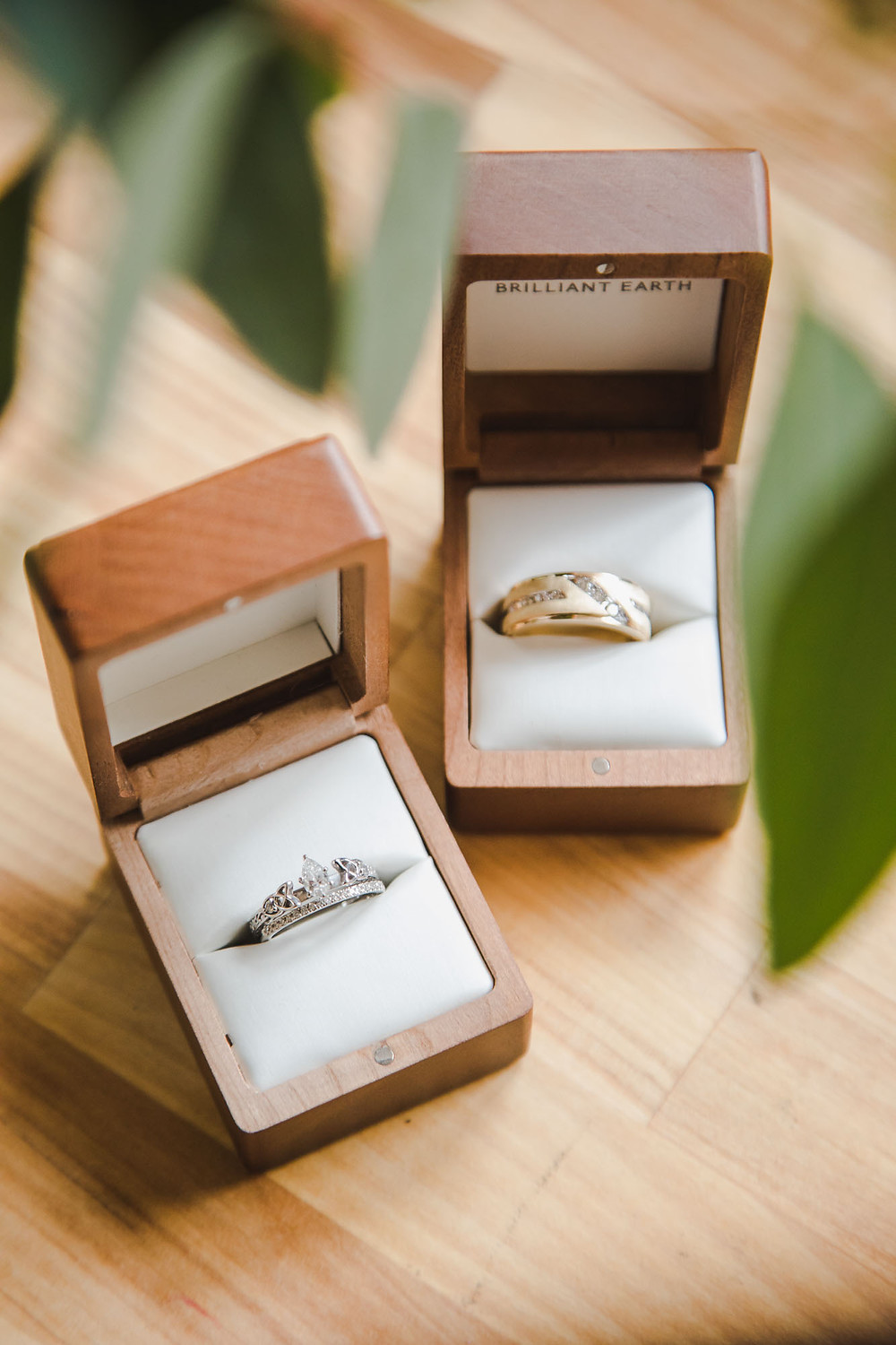 Wedding rings in wooden boxes on a wooden bench with leaves surrounding
