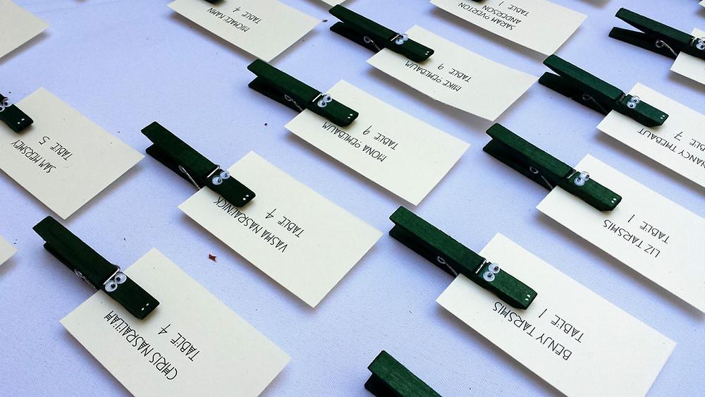 Handmade Gator clothespin craft clipped to wedding escort cards.