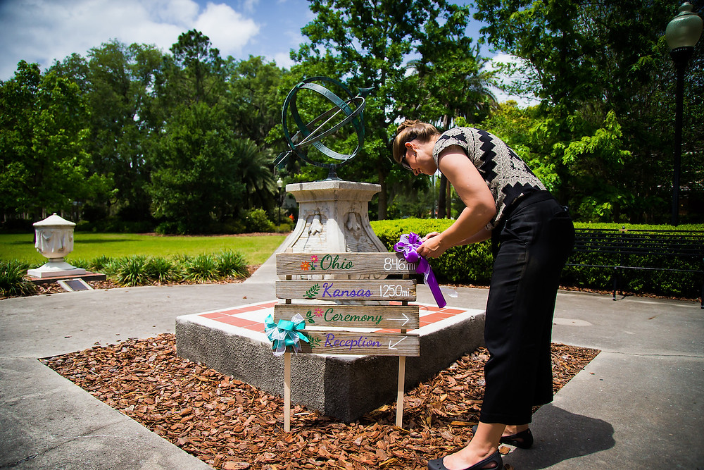 MasterPiece Weddings planner, Rachel Griffin, sets up a wedding decor location sign before a wedding ceremony at The Thomas Center in Gainesville Florida.