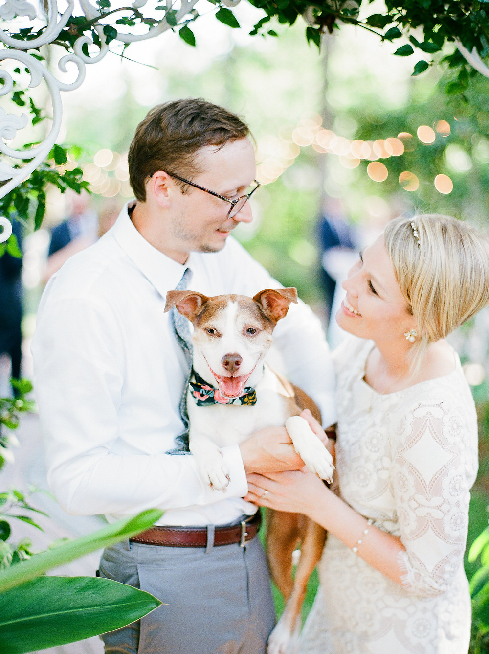 Couple smiling with their dog on their wedding day at Sweetwater Branch Inn in Gainesville Florida.
