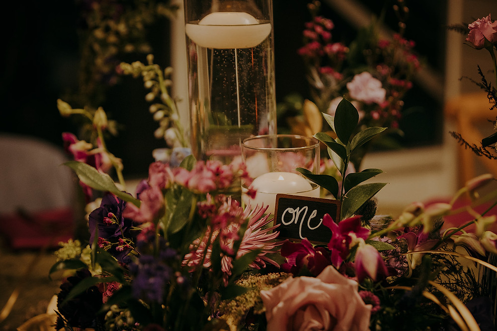 Enchanted Forest themed wedding centerpiece with floating candles and chalkboard table number.
