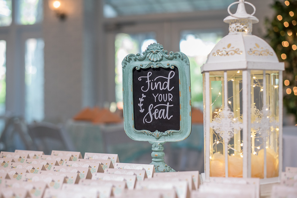 "Wedding chalkboard about escort cards with white lantern. The sign says ""Find Your Seat."""