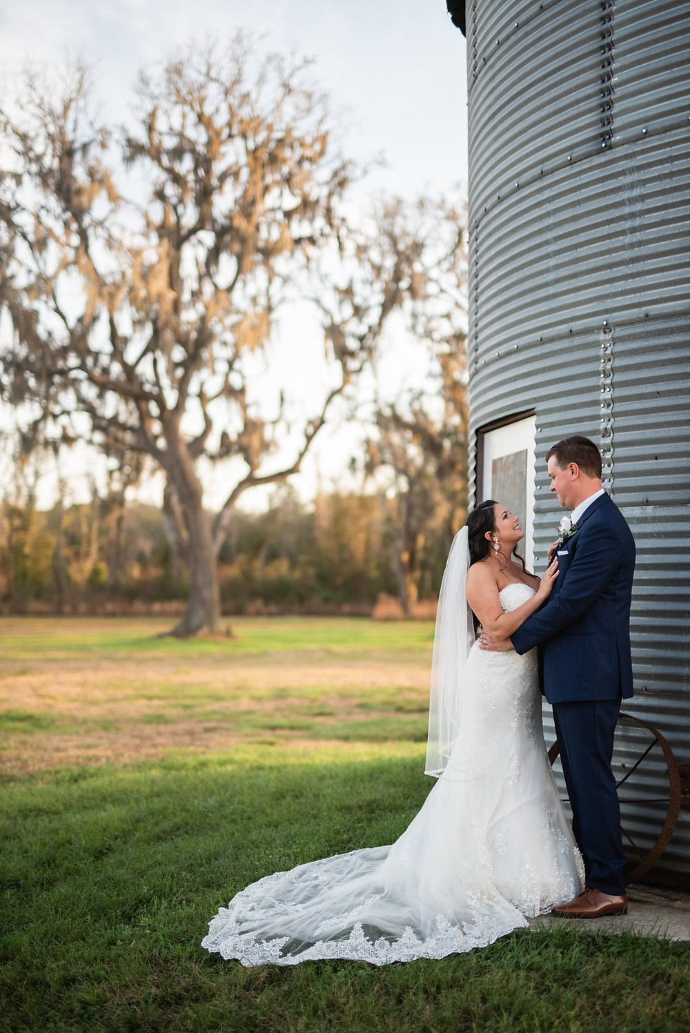 Bride & Groom looking at each other next to a Silo.