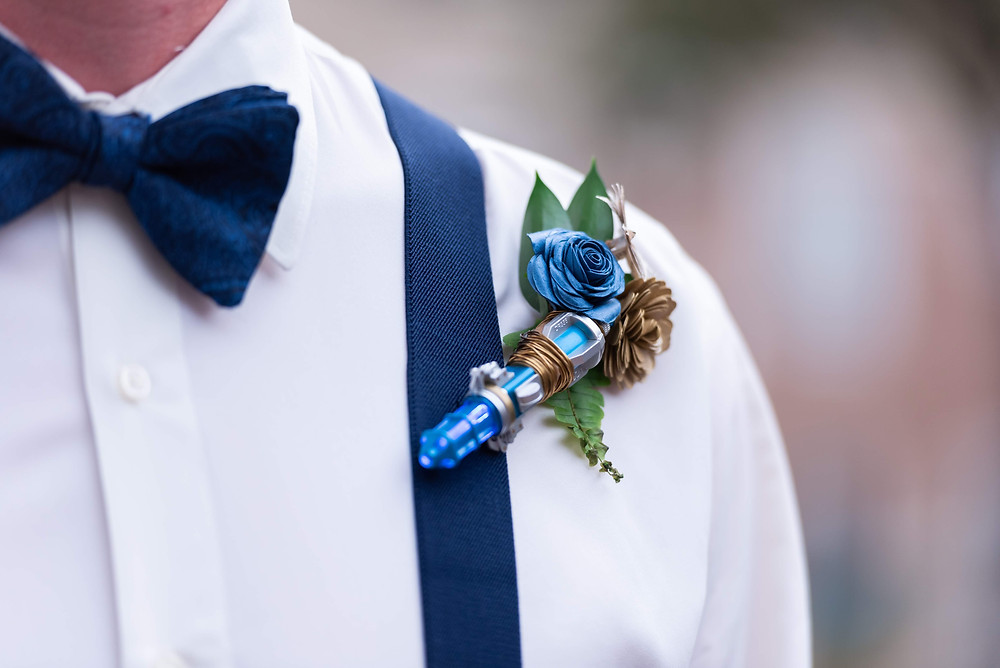 Groom with a handmade boutonniere made from a Dr. Who sonic screwdriver with navy blue accents.