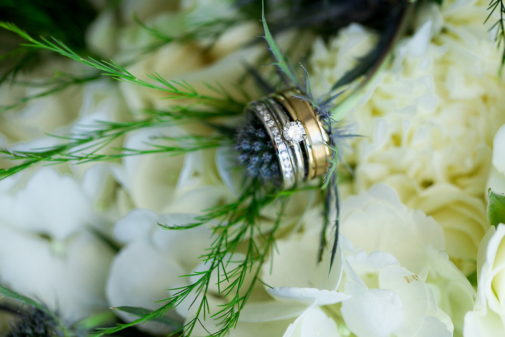 Wedding rings set in white hydrangeas and green flowers.