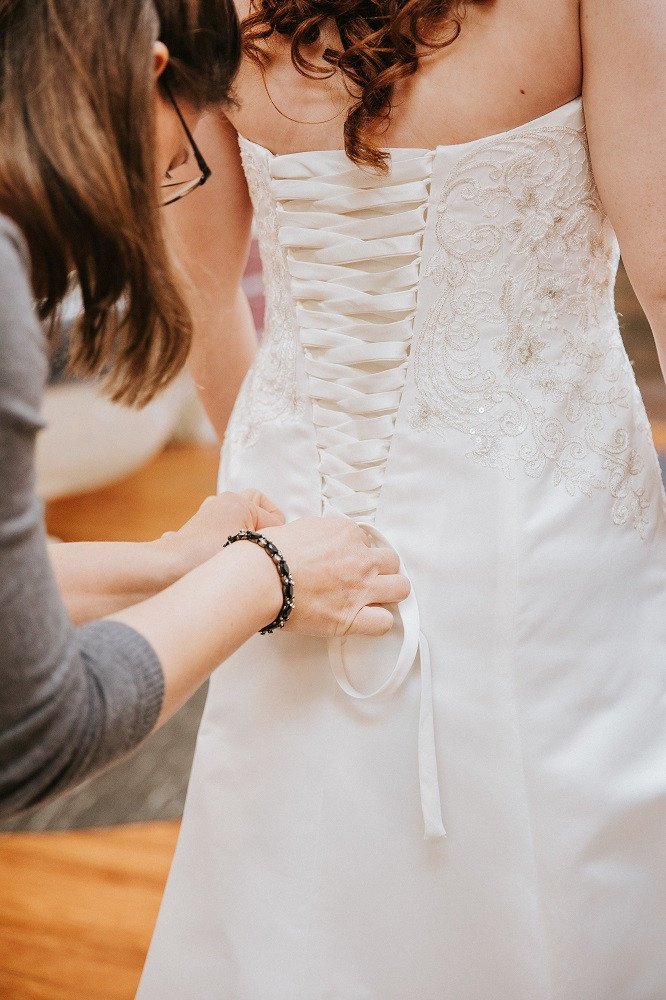 Gainesville wedding planner, Rachel Griffin with MasterPiece Weddings, laces up a corset on a bridal gown.