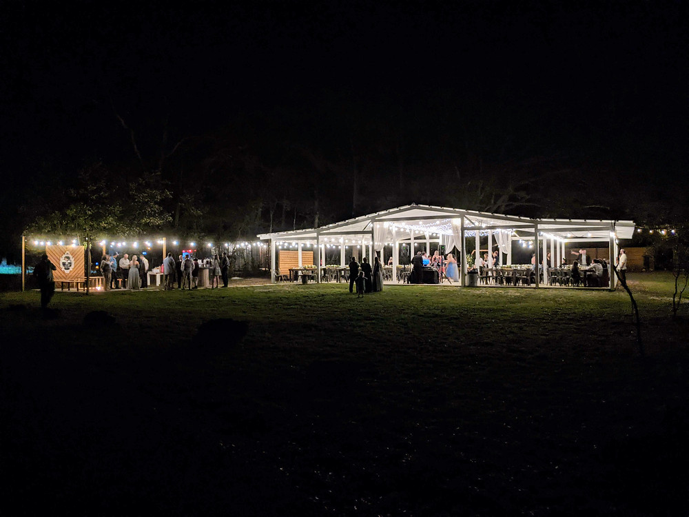 Wedding guests celebrate under the market lights at an evening wedding at West Light Farm.