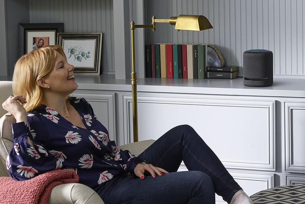 Woman listening to Echo Studio speaker in living room