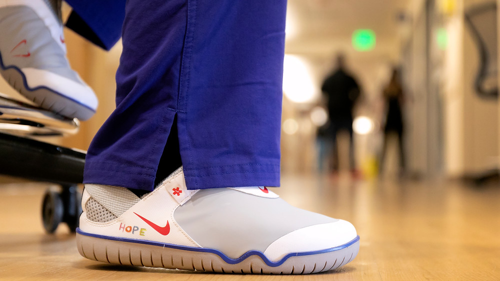 An Oregon Health 7 Science University nurse wears a version of the Air Zoom Pulse in a colorway created by OHSU Doernbecher patient Sawyer Miller.
