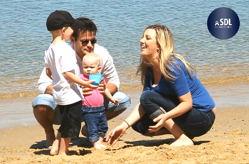 Blonde woman in blue shirt crouching on beach in front of man with dark hair and sunglasses, small infant in pink shirt, and toddler wearing black hat