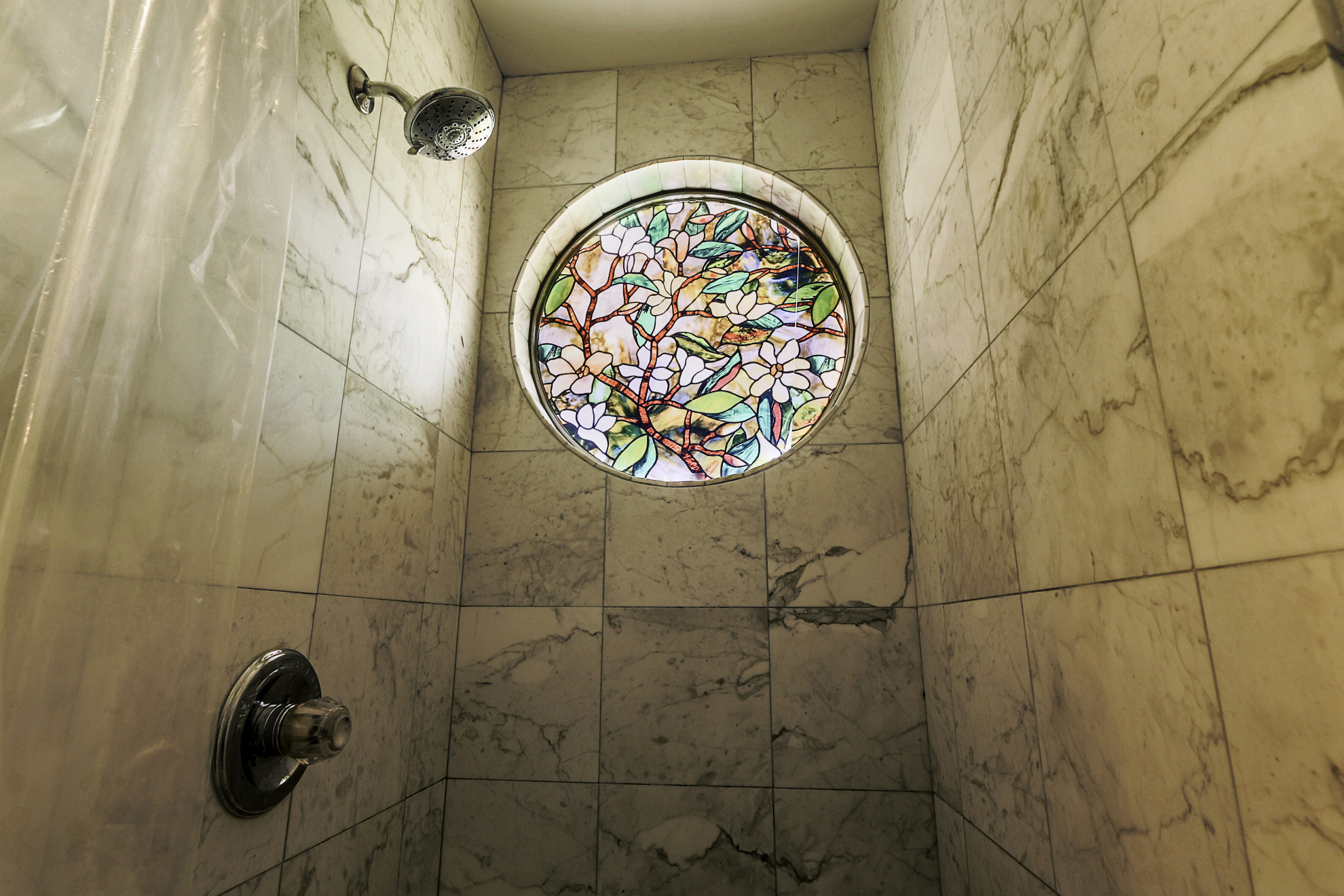 Stain glass shower window is surrounded by marble