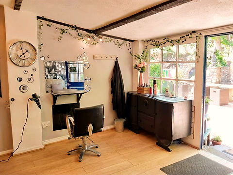 Sunny view from inside Henleys hairdressers - mirrors - black leather chair - garlands of ivy.