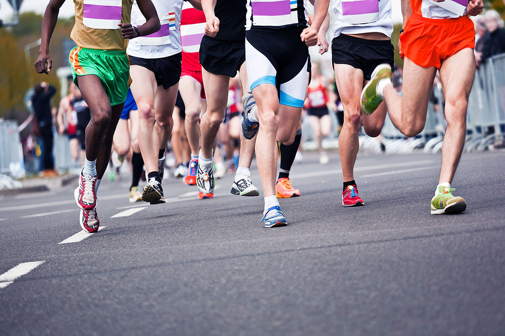 Photo of a group of runners' legs as they sprint down the street.
