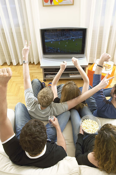 Rear view of young friends watching football match and celebrating in living room.jpg