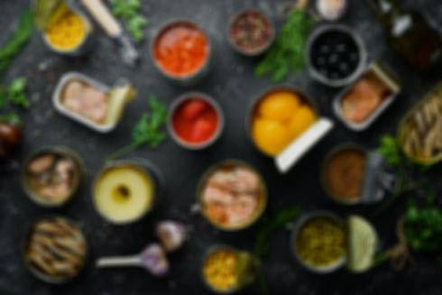Canned vegetables, beans, fish and fruits in tin cans on black stone background. Food stoc