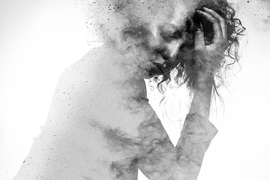 Imagem com efeito granulado com mulher negra triste e com a mão no rosto