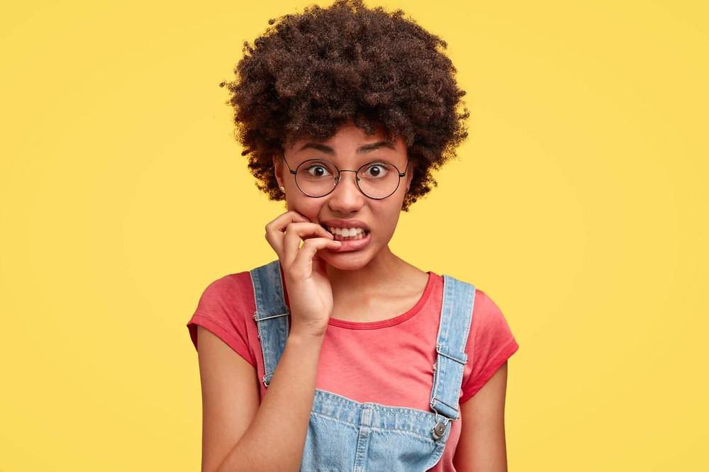 Jovem negra ansiosa de óculos redondo roendo as unhas
