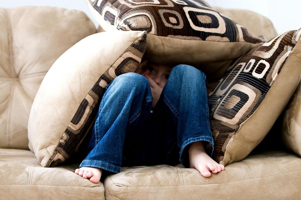 An anxious child hiding behind cushions