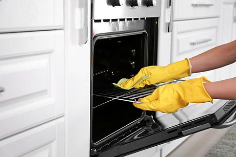 Woman cleaning oven in kitchen.jpg