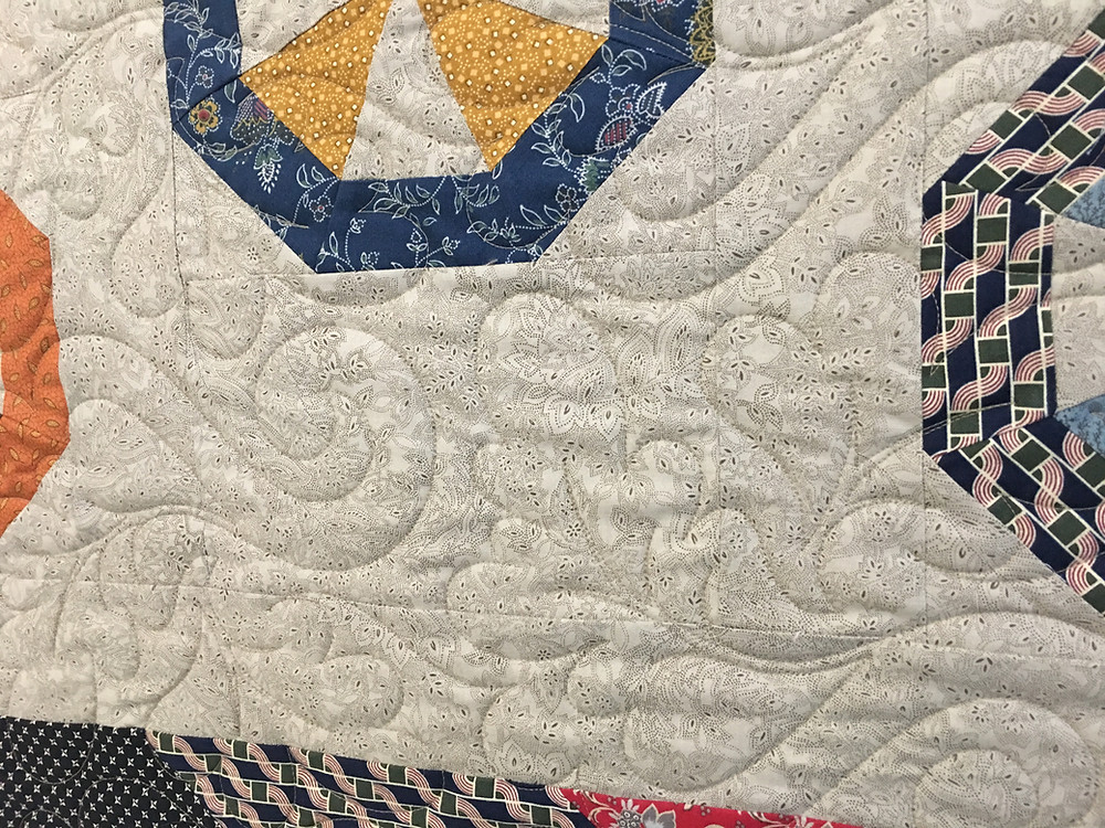 Oak Leaves quilting pattern on Scrappy Pinwheel Hedgehog Block quilt by Jill Seward