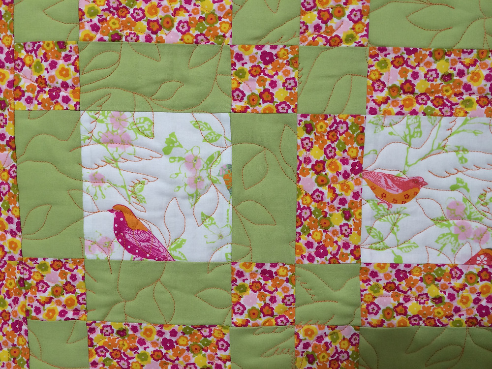 closeup of birds quilt with humming bird quilting