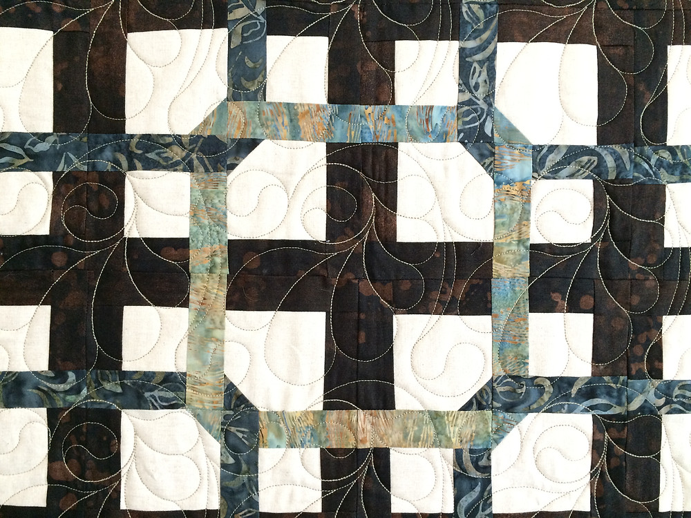 feather quilting design on repeating block quilt