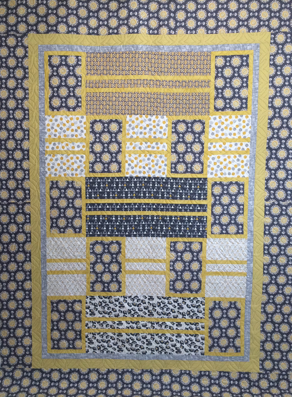 blue and yellow quilt with star burst prints
