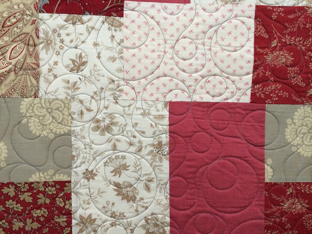 shades of red and white quilt with floating circles quilting