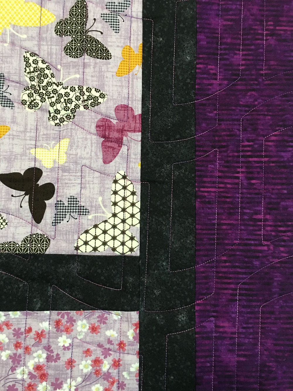 Another close up of quilting pattern in purple thread