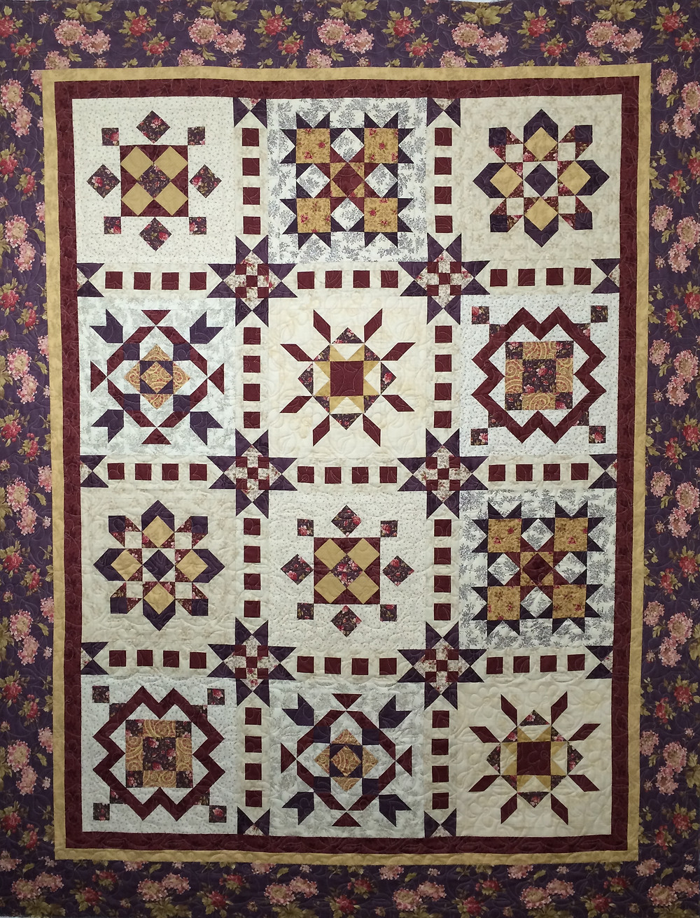 sampler quilt in shade of plum and white fabric