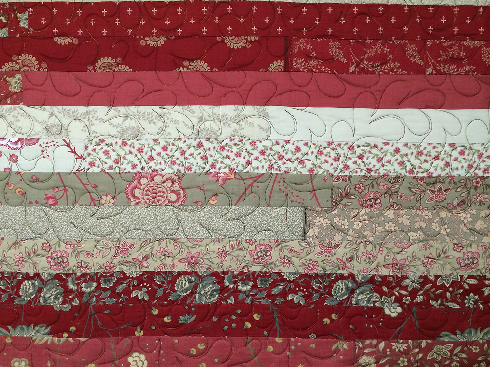 shades of red quilt with feather quilting pattern