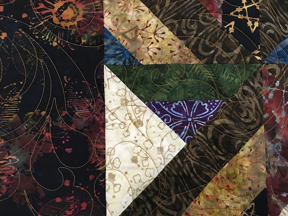 Feather quilting design on Batik block quilt by Terri Manley