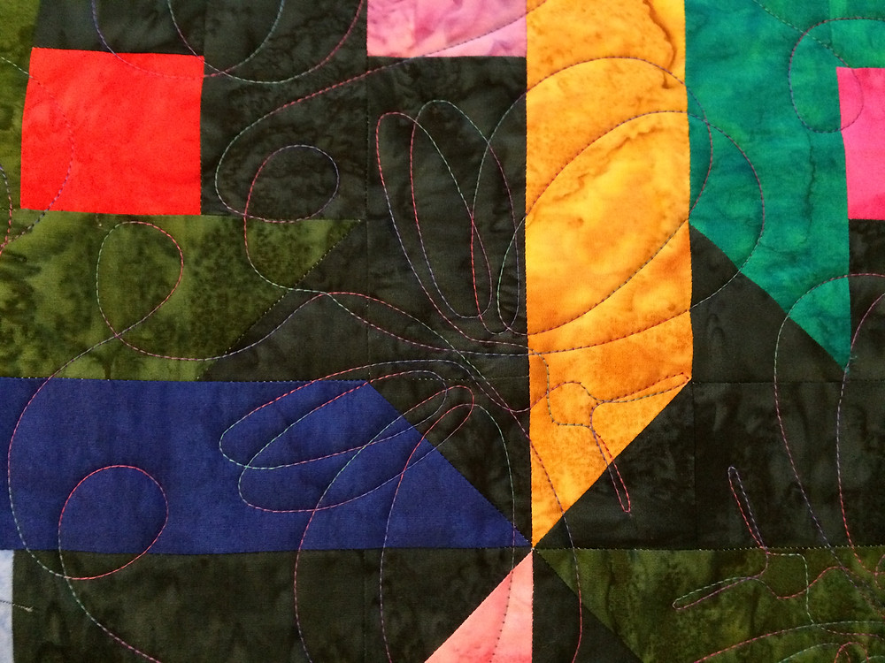 close up of butterfly quilting design on jewel tone batik quilt