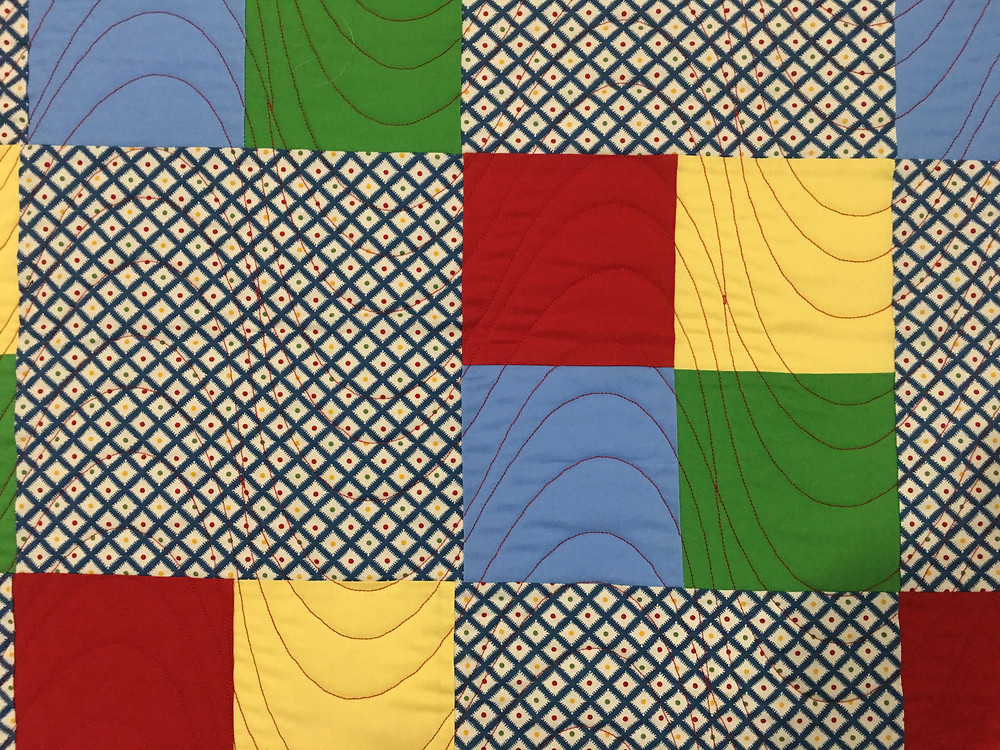 Wave quilting pattern on four patch quilt by Debbie Gaston