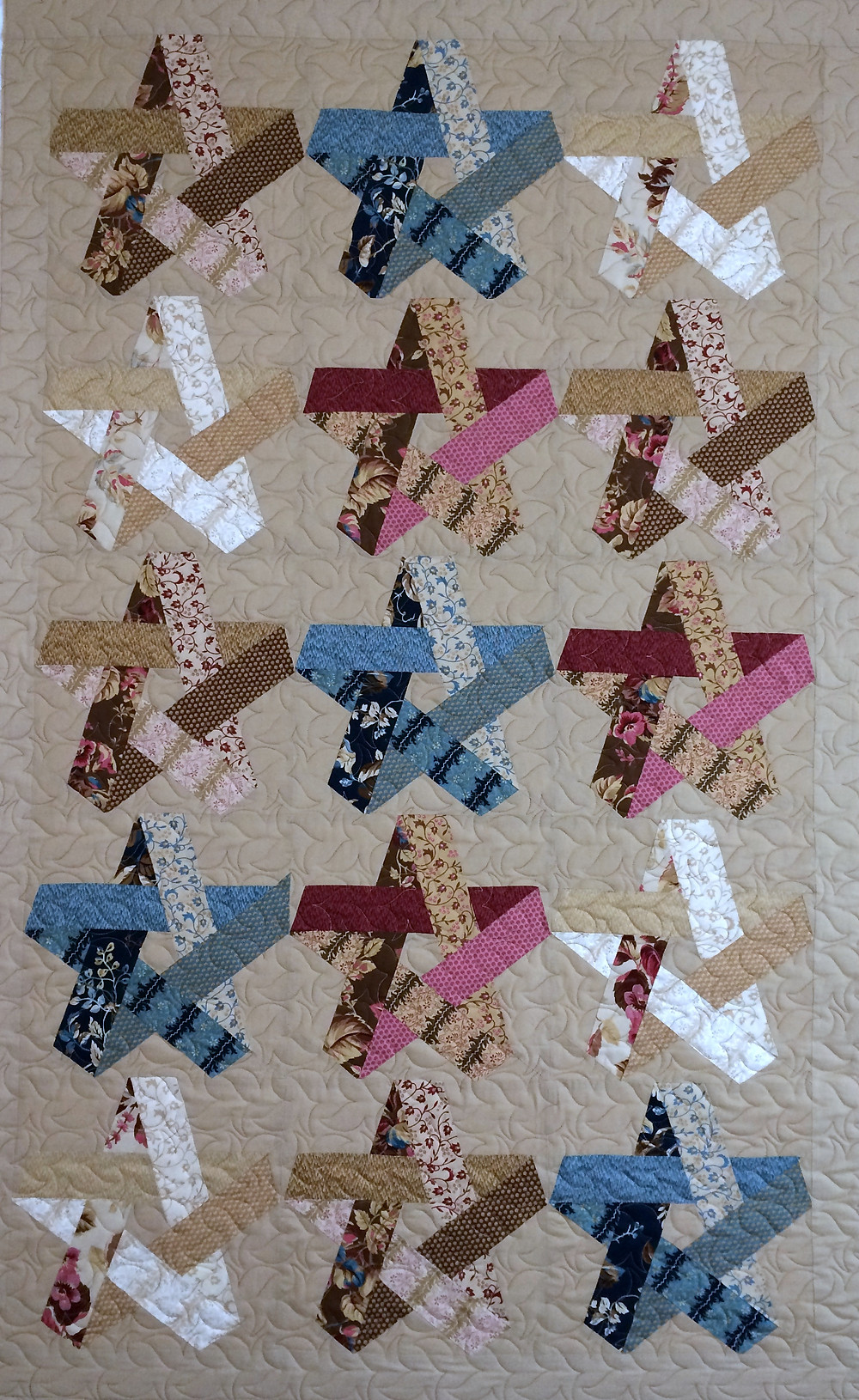 stars of colors in blue cranberry and beige quilt