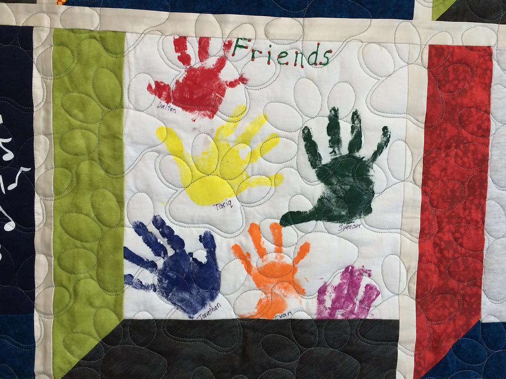 children autographed their hand print on school t-shirt quilt