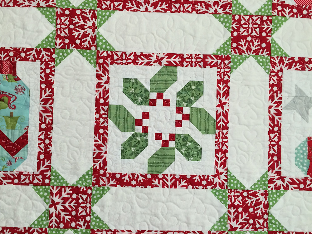 Closup of Deb Taylor Christmas Quilt with a holiday wreath