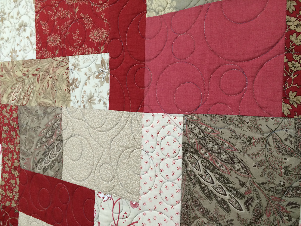 shades of red and white quilt with floating circles quilting on an angel