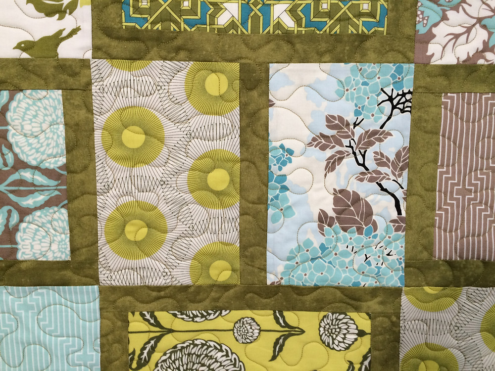 closeup of Jill Seward olive, yellow and blue quilt.