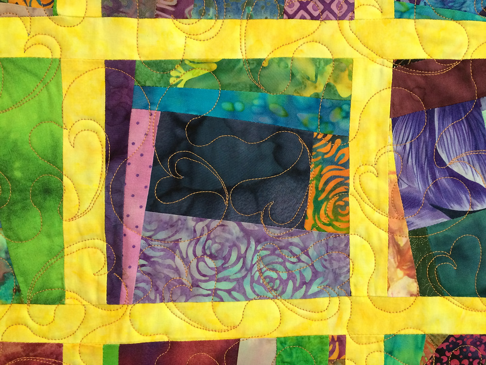 closeup of scrappy blocks with floating hearts quilting design