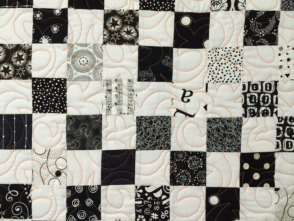 black and white quilt with fleur de lei quilting pattern