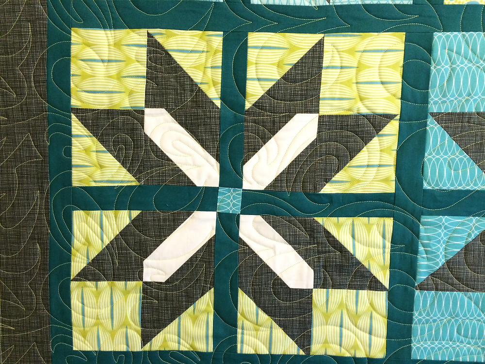closeup of For You Quilt with swirls quilting in light green thread