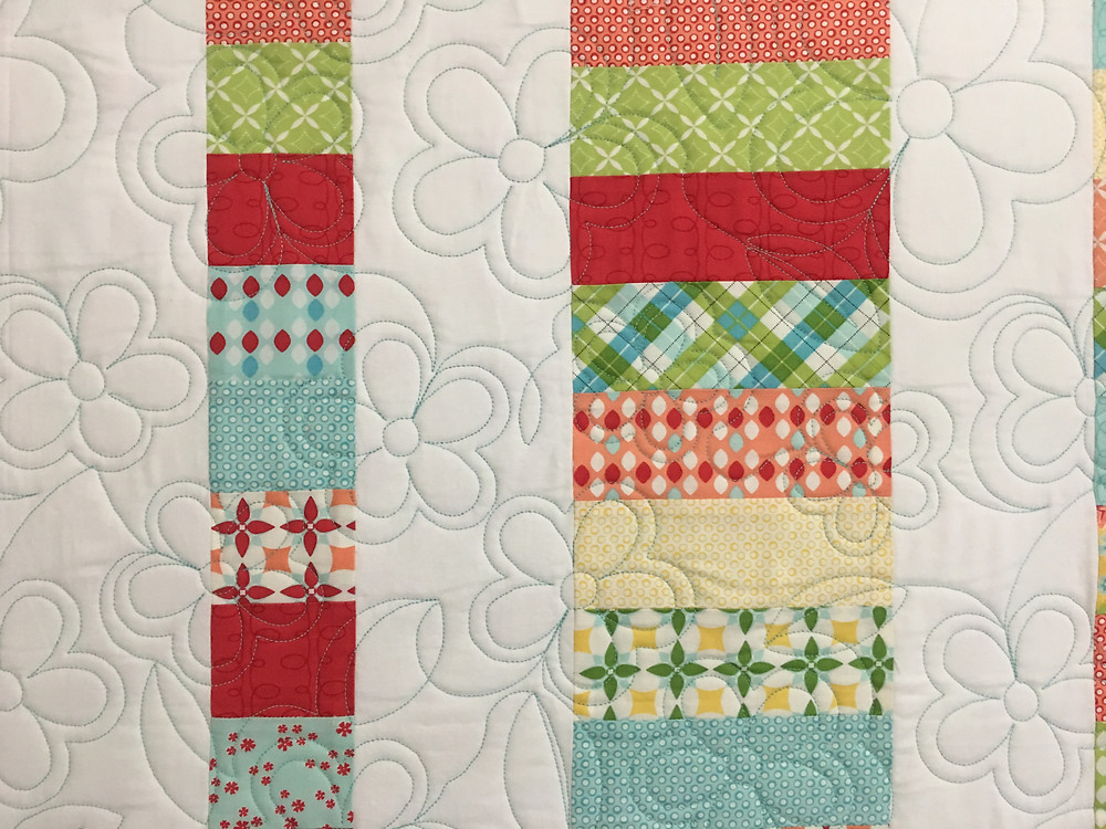 Another closeup of flowers quilting pattern on Jelly Roll quilt by Debbie Seitz