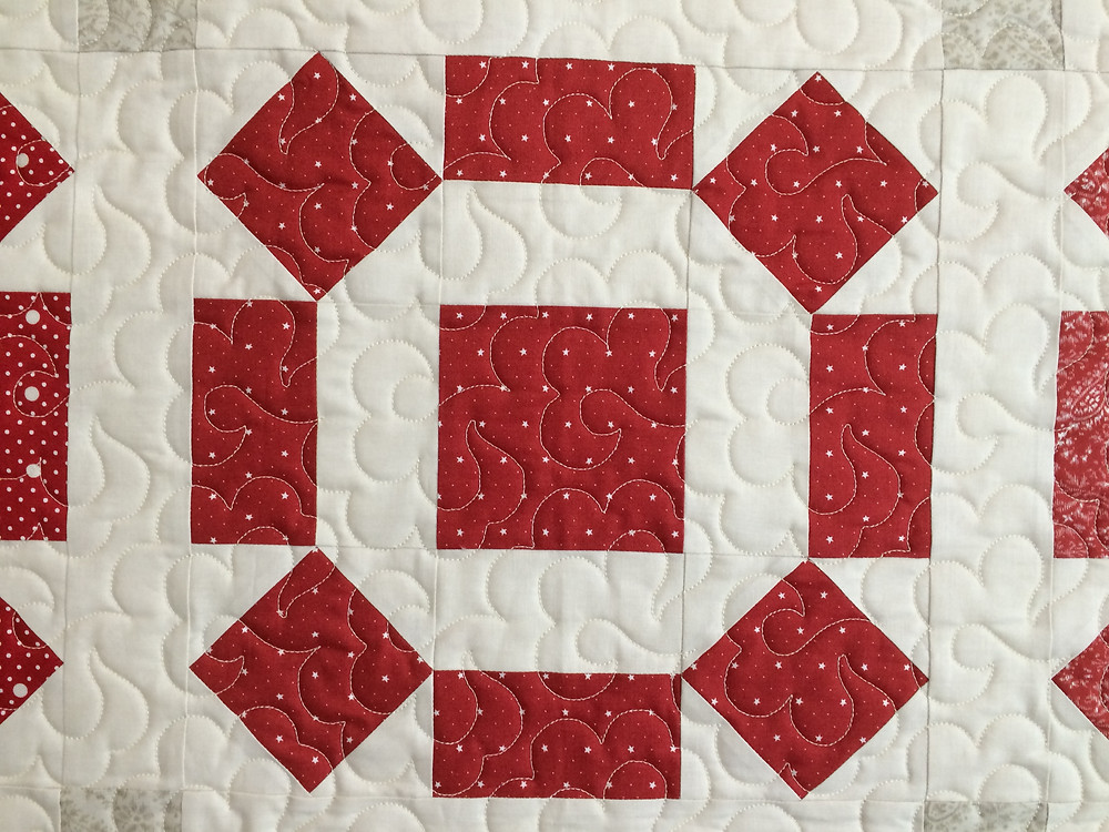 close up of red and cream quilt by Cheryl Cohorn