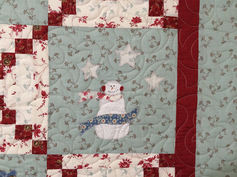 closeup of fleur de lei quilting design on bunny hill snowmen quilt