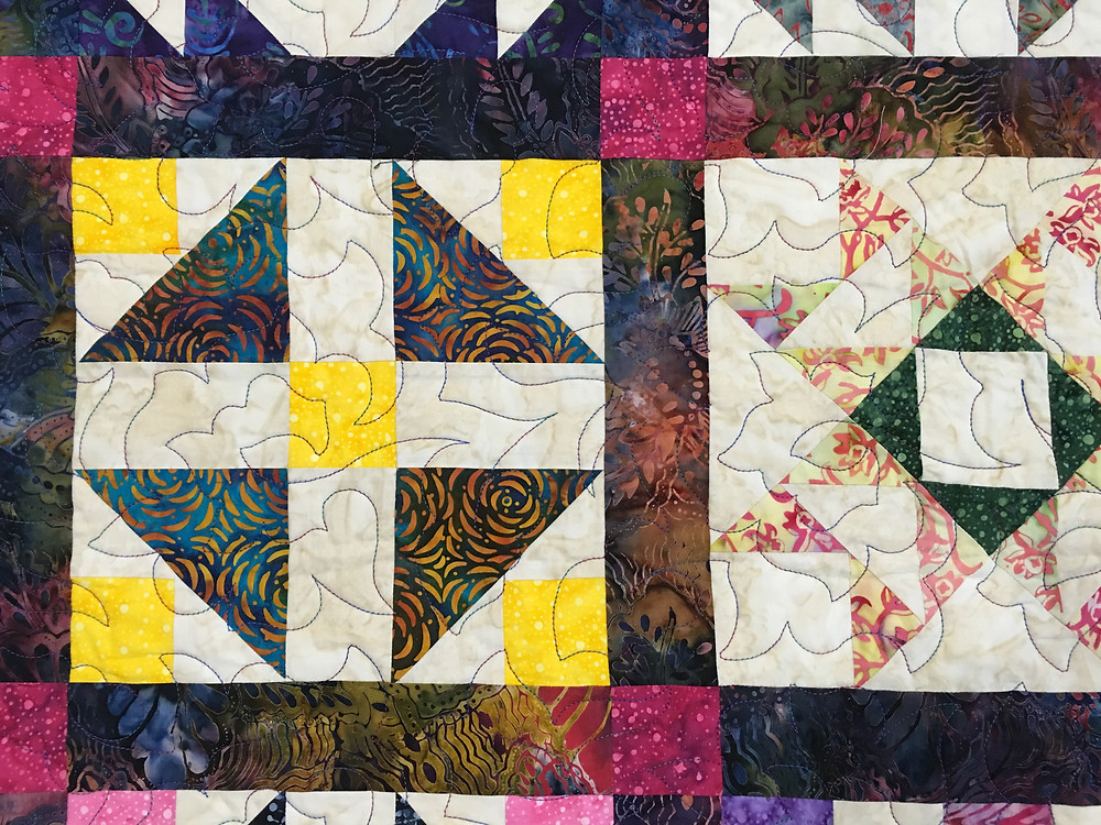 Quilting Pattern of Flowers on multi color batik quilt by Debbie Seitz