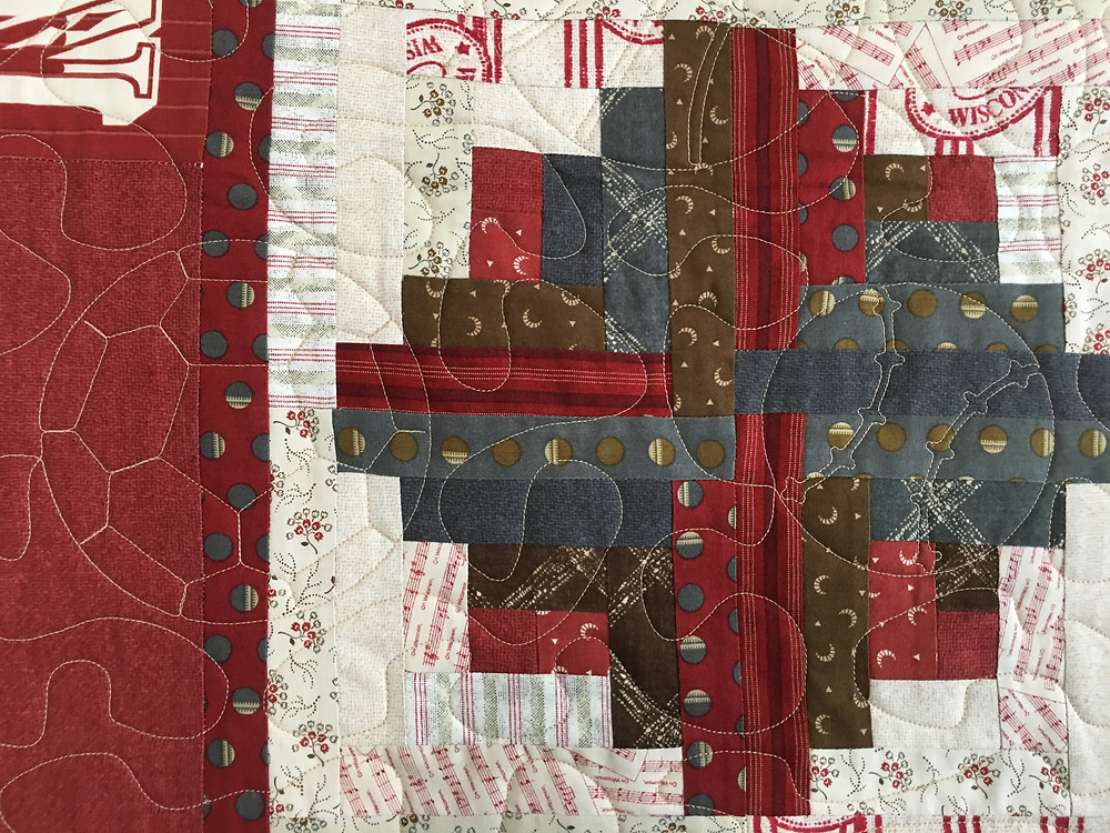 Sports quilting pattern on Log Cabin quilt by Joan Salesman