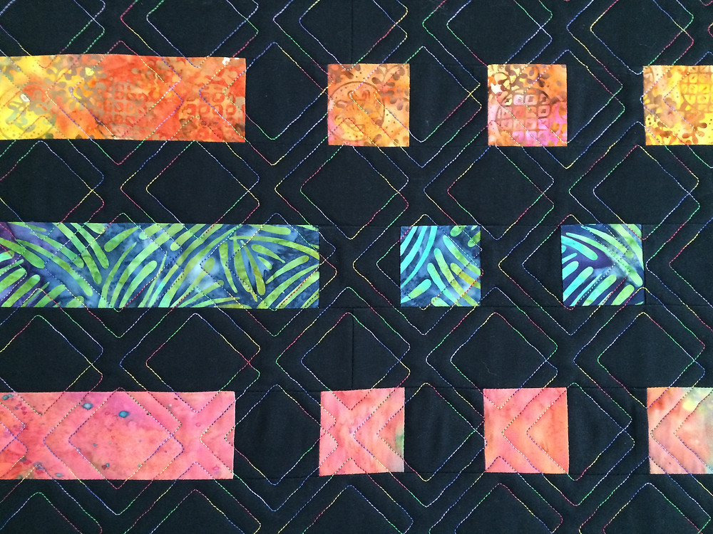 closeup of geometric quilting design with multicolor thread on the morse code quilt