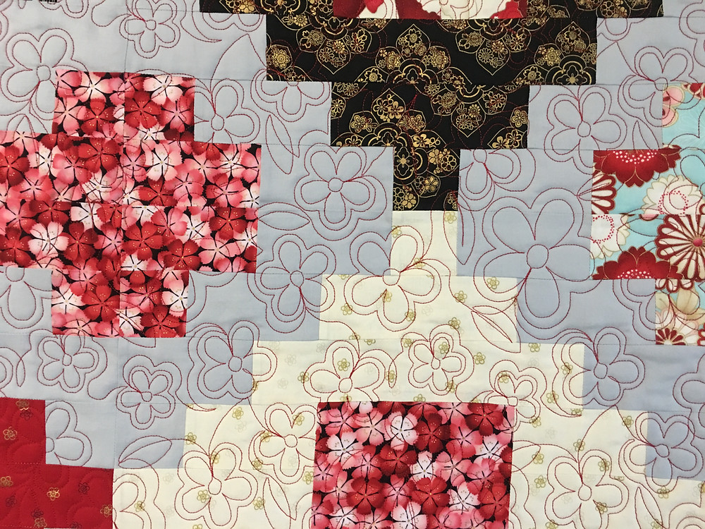 Flower Quilting Pattern on Stacked Red and Black Quilt by Cynthia Parra