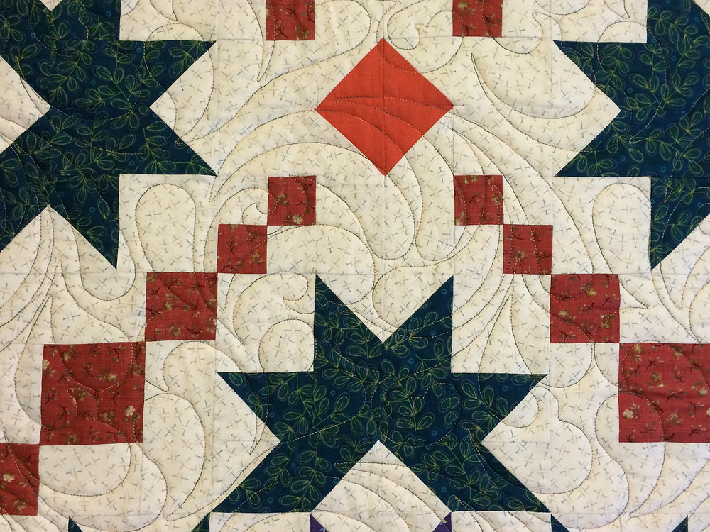 closeup of quilting feathers design on ohio star quilt